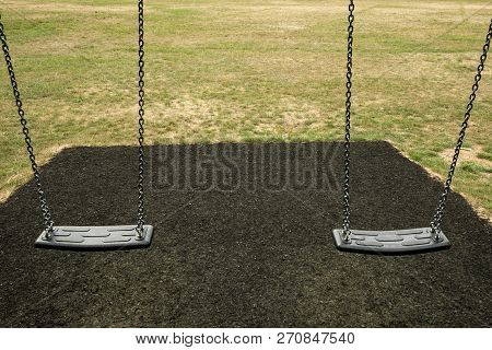 Two Swings In Playground Over Black With Grass In Background