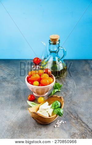 Mozzarella Olive Oil Tomato Basil Leaves On Blue Background. Italian Salad. Mediterranean Salad. Ita