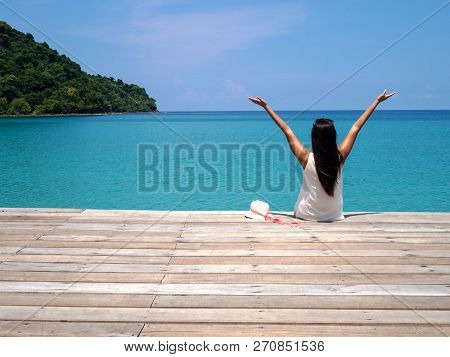 Young Asian Woman With Long Black Hair Sitting On Bench Facing Sea And Raise Her Hands In Sunny Day