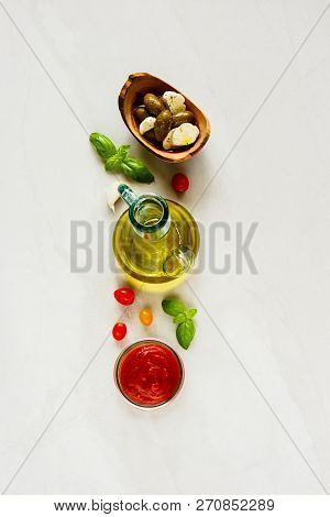 Italian Cooking Ingredients - Tomato Sauce, Olives, Mozzarella, Basil Leaves And Oil Flat Lay.