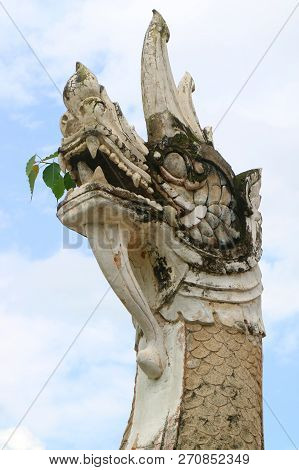 Small Plants Growing In The Mouth Of Naga Sculpture In Wat Phumin Buddhist Temple, Historic Place In