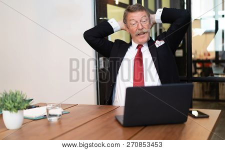 Senior Business Man  Sitting At Workplace In Front Of Computer While Relaxing.