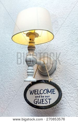 Glowing Lamp With Lampshade On The White Wall And Post Welcome. Wooden Welcome Sign.