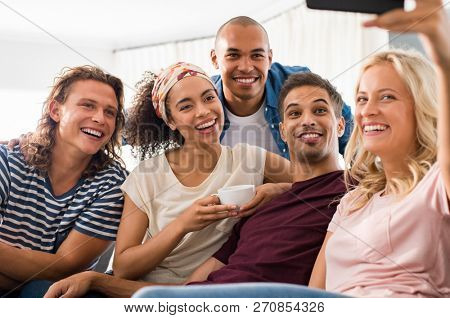 Group of multiethnic friends taking selfie at home. Smiling men and young women with smart phone taking selfie while sitting on couch. Group of funny boys and happy girls taking photo smartphone.