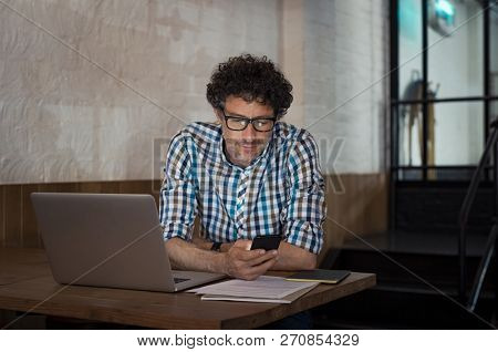 Mature casual businessman using smartphone and working on laptop at cafe. Business man looking at cellphone. Checking message on smartphone while working on document and paperwork during the night.