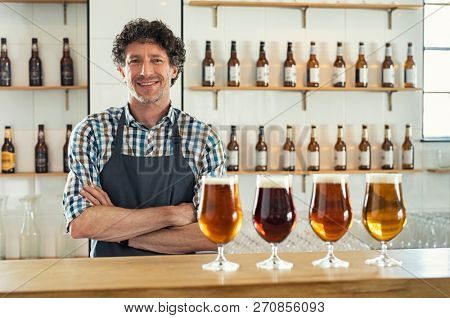 Smiling bartender wearing apron standing behind counter with beer bottles on shelves and craft beer in glasses at counter. Portrait of cheerful barman standing with different types of draught beer.