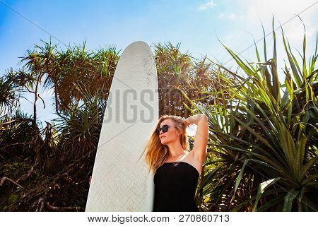 Surfer Girl In Black Bikini With Surfboard Posing By Palms On Beach With Sun. Young Woman Look At Se