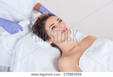 The doctor-cosmetologist makes the procedure Microcurrent therapy On the hair of a beautiful, young woman in a beauty salon.Cosmetology and professional skin care. poster