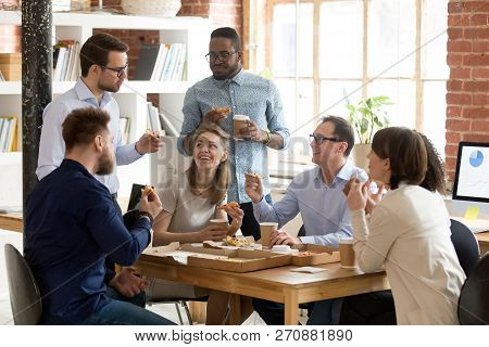 Multiracial Work Team Eating Pizza Together On Break
