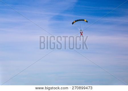 Santa Claus Arrival By Parachute. Santa Clause Parachuting In The Air. The Concept Of Christmas Spir