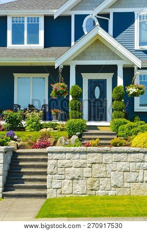 Entranc Of Luxury Family House With Landscaped Front Yard On Land Terrace. Family House On Blue Sky