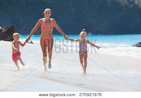 Happy Family - Young Mother, Daughter, Baby Son Hold Hands, Run Together With Splashes By Water Pool