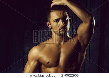 Portrait of handsome sexy sensual muscular stylish young man topless with bare torso and beautiful body standing indoor on wooden background, horizontal picture poster