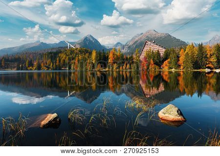 Picturesque autumn view of lake Strbske pleso in High Tatras National Park, Slovakia. Clear water with reflections of orange larch and high mountains on background. Landscape photography