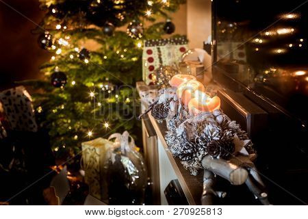 Four Burning Advent Candles, Beautiful Decorated Setup Lights In Background Christmas Tree With Gift