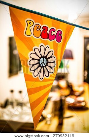 Hippie Peace Text And Love Flower Power Van On A Hanging Party Sign Over A Blurred Background