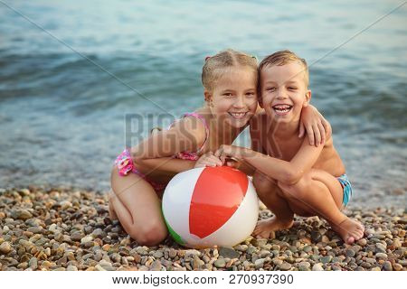 Brother And Sister Playing Ball On The Beach