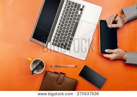 Businessman Working Using Digital Tablet, Laptop And Mobile Phone On Colored Desk. View From Above