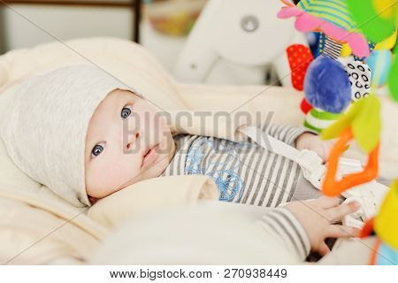 Baby Laying In Bouncer Chair And Playing Toy
