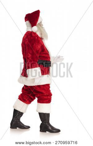 side view of fat merry santa claus walking on white background, full length picture