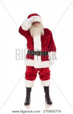 merry saint nick wearing santa costume stands on white background and holds hand on forehead while looking far away, full length picture poster