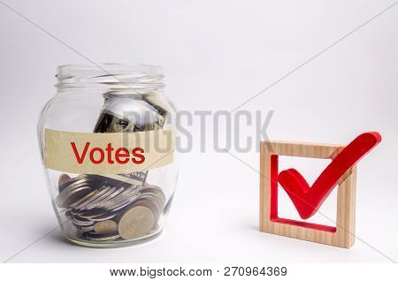 Glass Jar With Coins And The Words Votes And A Checkbox. Concept Of Voting For Money. Bribing Voters