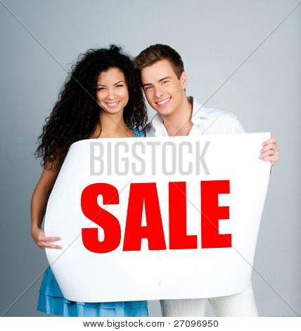 """young couple with a placard """"sale"""" on a lihgt poster"""