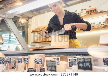 Young shop clerk in deli cutting cheese at the counter with a knife