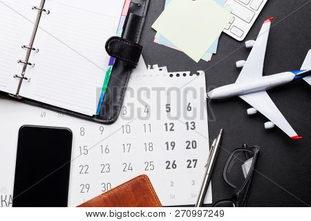 Business trip concept. Accessories on desk table. Glasses, passport, notepad, smartphone and airplane toy. Top view with copy space