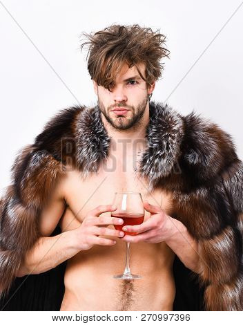Sexy sleepy rich macho tousled hair drink wine isolated on white. Health and wellbeing. Richness and luxury concept. Guy attractive rich posing fur coat on naked body. Rich athlete enjoy his life poster