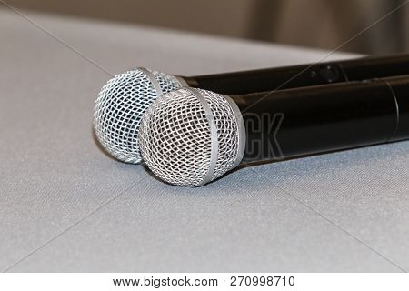 Pair Of Microphones Lies On Tablecloth Of Conference Room Table For Speakers. Microphones For Press