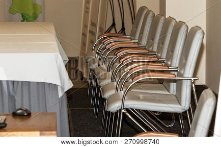A Row Of Modern Metal Office Chairs Near The Table In A Conference Room. Blank Illustrative Backgrou