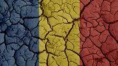 Political Crisis Or Environmental Concept: Mud Cracks With Romania Flag poster
