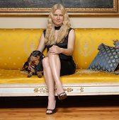 Young blonde woman with a little dog sitting on an elegant yellow sofa. poster
