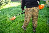 Man with trimmer mows grass in yard. Gardener with lawnmower poster