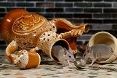Two mice on countertop in the kitchen. One mouse comes out of an overturned ceramic jug. The second mouse overturned the cup. poster