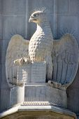 an architectural statue on the side of an old church depicts an eagle holding open a book. poster