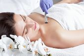 The cosmetologist makes the Microdermabrasion procedure of the facial skin of a beautiful, young woman in a beauty salon.Cosmetology and professional skin care. poster
