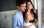 Romantic young couple being intimate and sensual in bedroom poster