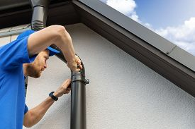 Worker Installing House Roof Gutter On The Wall