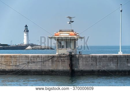 A Small Bulit Structure On A Pier With The Darling Pier Lighthouse In The Background On Fushan Bay I