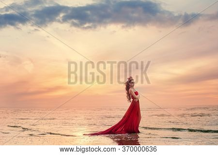 Romantic And Beautiful Woman In Fluttering Red Dress Stay Along On Sea Wave Beach At Sunset. Fairyta