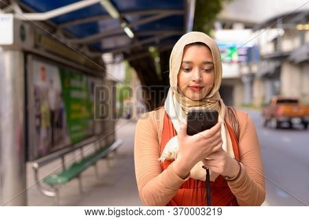 Young Beautiful Indian Muslim Woman Using Phone While Waiting At The Bus Stop