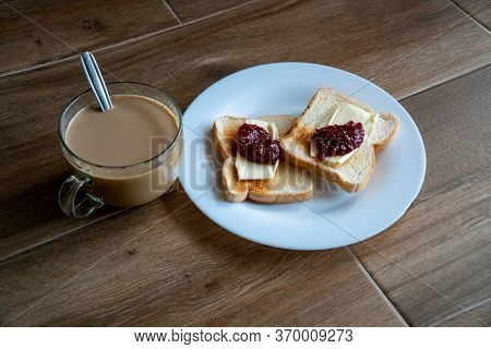 Cup Of Coffe With Milk And Two Slices Of Toasted Sandwich Bread With Butter And Raspberry Jam A Whit