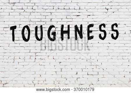 White Brick Wall With Inscription Toughness Handwritten With Black Paint