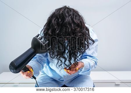 Woman Makes Herself Curly Hairstyle.woman Drying Hair At Home. Woman Styling Her Curly Hair With Hai