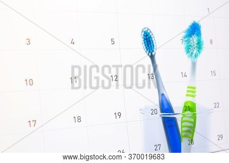 New & Old Toothbrush (damaged) In Clear Glass For Teeth Cleaning Isolated On Calendar (write A Messa