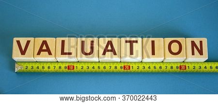 Valuation Word On Cubes Arranged Behind The Ruler On Blue Background.