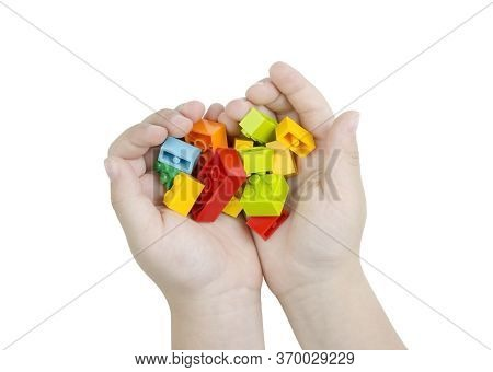 Childrens Hands Hold A Handful Of Colorful Toy Cubes. Isolated Hands On A White Background Without A