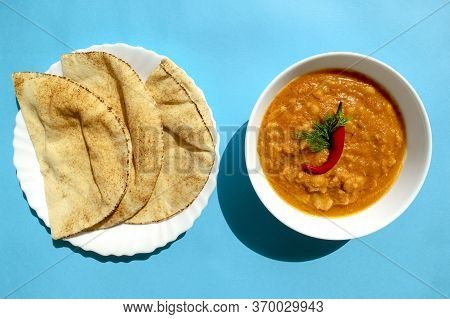 Famous Traditional Arabic Cuisine - Peeled Fava Beans With Chilli In White Bowl And Pita Bread On Bl